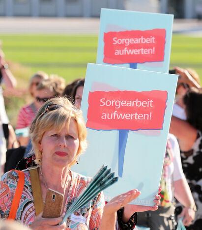 Eine Gruppe von ca. 10 Personen halten Plakate in den Händen mit den Aufschrift 'Sorgearbeit aufwerten'.